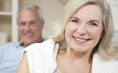 Older woman smiling with husband in background