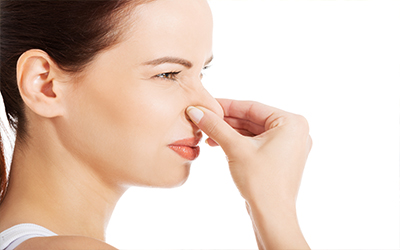 A woman plugging her nose